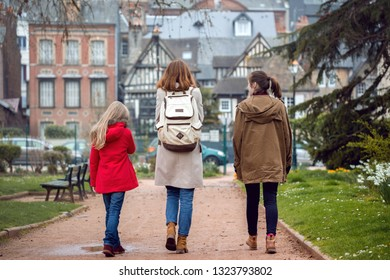 happy mother and daughters walking around the french city Honfleur, France