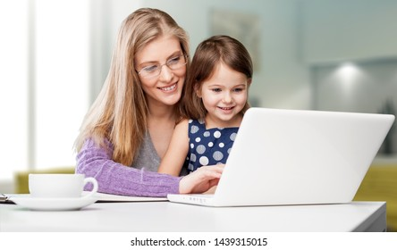 Happy mother with dauther using laptop at home