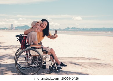 Happy mother and disabled teenage boy on wheelchair use social media, Sea beach background,Lifestyle activities in travel of handicapped teen family, Take a selfie by mobile phone.