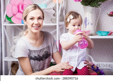 Happy mother with drinking water daughter