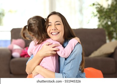 Happy mother embracing to her baby daughter in the living room at home