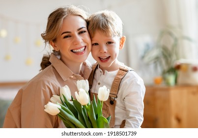 Happy mother  embracing son in gratitude with tulips,  smiling   and   looking at camera while celebrating holiday at home - Shutterstock ID 1918501739