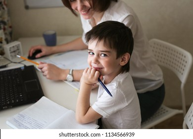 happy mother is engaged in a laptop with her son preschooler, a real European interior, the concept of childhood and learning