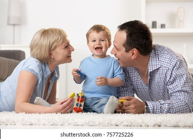Happy mother father and baby boy having fun together at home