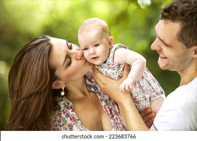 happy mother and father with baby in park