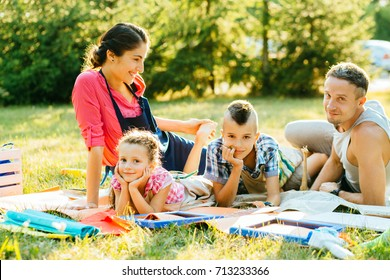 Happy mother, father and two kids are painting in the park. The concept of a happy family.