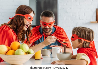 happy mother feeding son with flakes while sitting at kitchen table in superheroes costumes