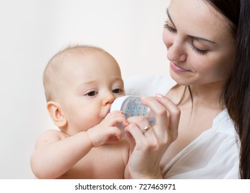 happy mother feeds her baby son from bottle