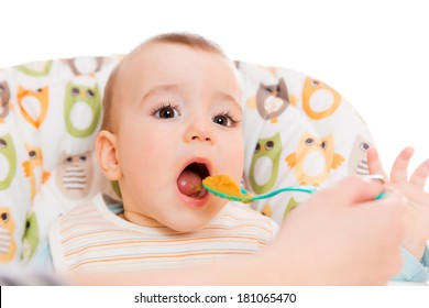 Happy mother feeds hungry baby from a spoon