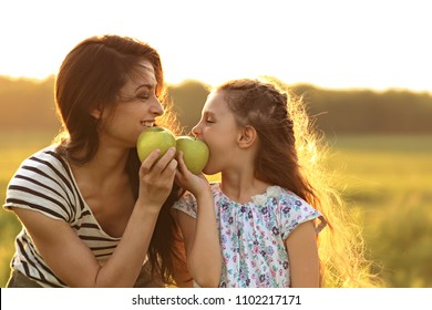 Happy mother and fun enjoying kid girl have a picnic and eating the green apples on summer time sunny background