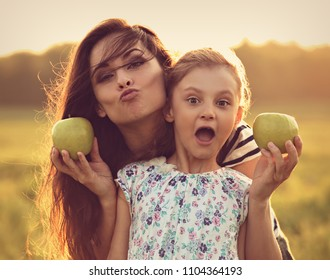 Happy mother and fun excited kid girl have a picnic and eating the green apples on summer time sunny background. Closeup toned portrait