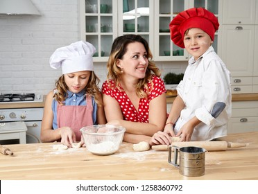 Happy mother with funny kids are preparing the dough, bake cookies in the kitchen