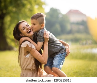 Happy mother getting kissed by her son