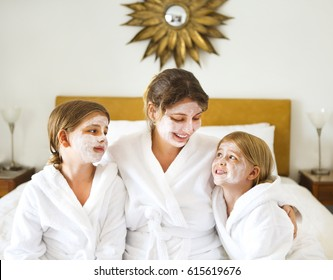 Happy mother and girls in bathrobes with cream mask. Family care and spa concept