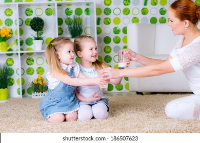 Happy mother  give glasses of milk daughters at home. Parent and children. Beautiful family model.