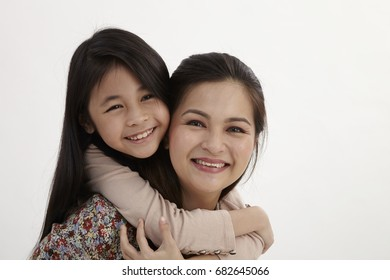 Happy mother giving piggy back ride to her daughter isolated on white background