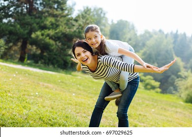 Happy mother giving a piggyback ride to her daughter