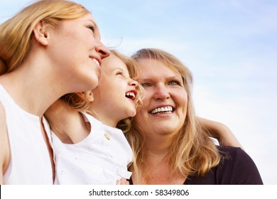happy mother, grandmother and little girl looking up, outdoor