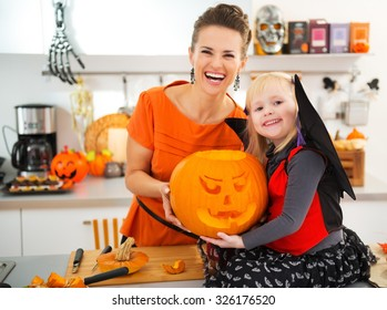 Happy mother with halloween dressed daughter holding big orange pumpkin Jack-O-Lantern for party in decorated kitchen. Traditional autumn holiday