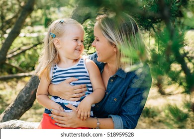 Happy mother having fun with cute blonde kid girl. Young woman playing with daughter. Happy parenting concept