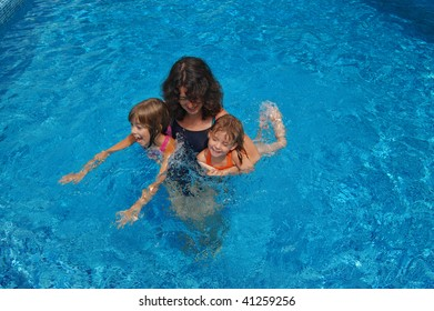 Happy mother having fun with her kids in swimming pool