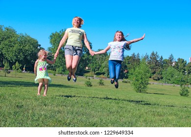 Happy mother having fun jumping with her daughters on green grass. Happy family team. Family enjoying summer vacations. People enjoying family holiday