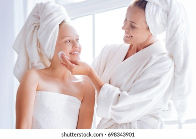 Happy mother helping her daughter to clean face