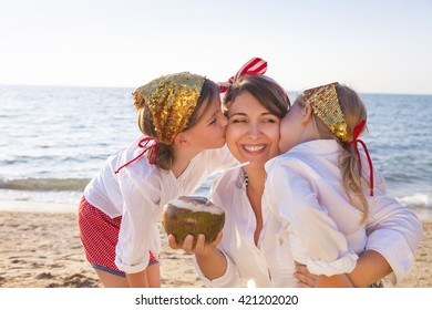 Happy mother with her adorable daughters drinking coconut milk on the beach