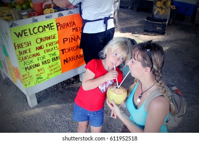 Happy mother and her adorable toddler daughter drinking fresh coconut juice at traditional street market. Travel to Mexico