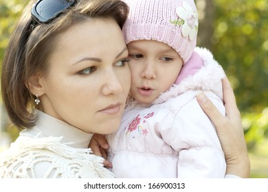 happy mother with her baby daughter for a walk in the autumn
