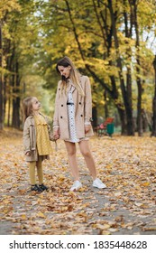 Happy mother and her beautiful daughter have fun and walk in the autumn park.