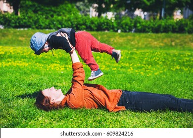 Happy mother and her child playing on meadow in the park at spring time. Prague, Czech Republic. Beauty nature scene with family outdoors lifestyles. Family background.