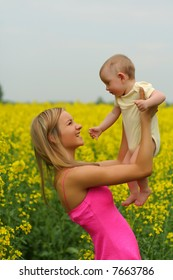 Happy mother with her child in yellow flowers field