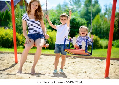 Happy mother and her children on playground