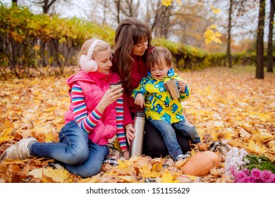 Happy mother with her children on a picnic. family tea party in the garden in autumn