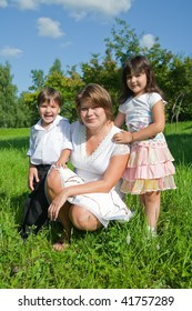 Happy mother with her children  sit in grass