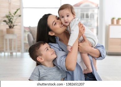Happy mother with her cute children at home. Family time