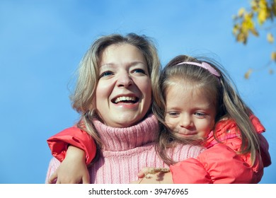 Happy mother with her daughter against autumn sky