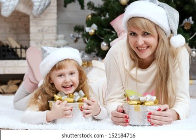 Happy mother with her daughter by the fireplace under the Christmas tree