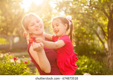 happy mother and her daughter eating strawberries in orchard garden. playing together in summer park.