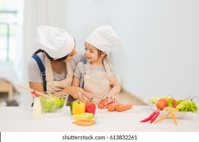 Happy mother and her daughter enjoy making and having healthy meal together at their home