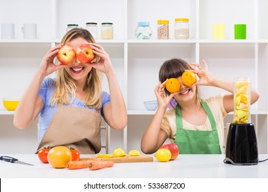 Happy mother and her daughter having fun while making smoothie together at their home. Mother and daughter making smoothie and having fun