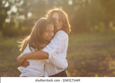 happy mother with her daughter hugging a teenager in the summer in the setting sun