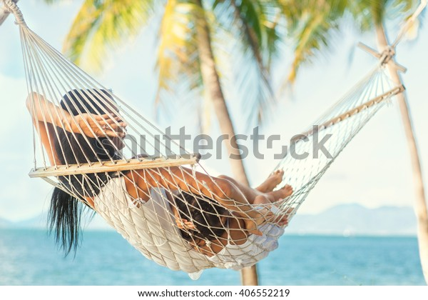 happy mother with her daughter lying in a hammock on the shore of a tropical beach. Mothers day.
