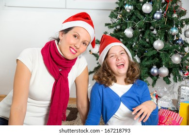 Happy mother with her daughter near Christmas tree