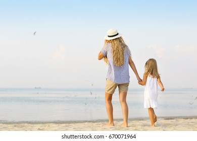Happy mother and her daughter on beach. Summer holiday and vacation concept