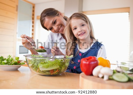 Happy mother and her daughter preparing a salad in their kitchen