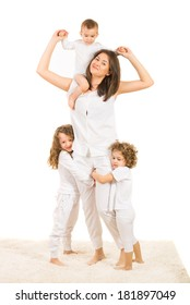 Happy mother with her kids playing home and standing on carpet against white background