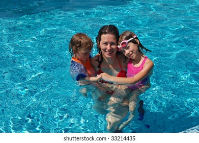 Happy mother with her kids in swimming pool