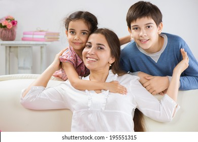 Happy mother with her little children at home